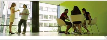 Students in a conversation in a green room with a big window.
